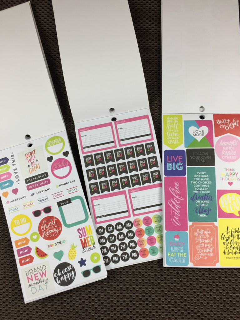 Three sticker books open showing stickers to be used in a planner